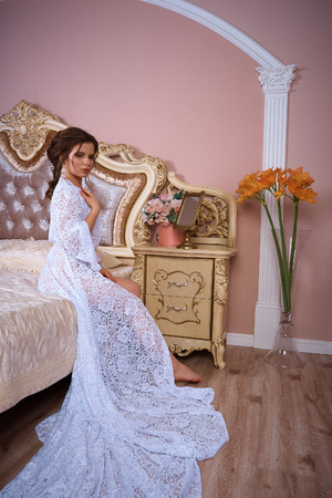 A portrait of a young pretty brunette in a long white dress Banco de Imagens