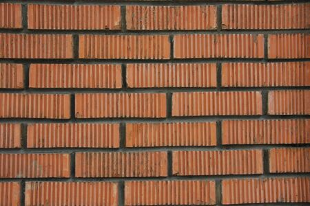 A wall of red brick and corrugated on the solution
