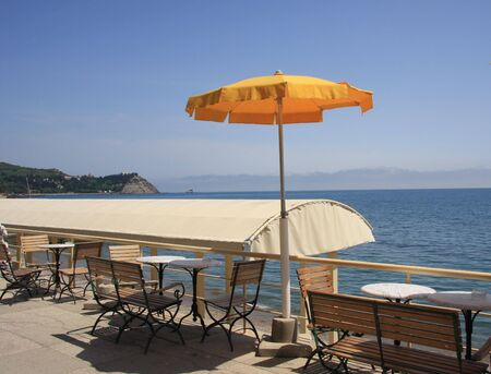 The yellow umbrella on the beach promenade with cafes