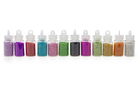 Beads different colorsr in bottles for the design of nails. White background. Stock fotó