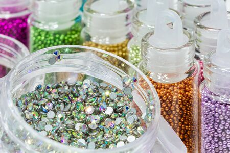 Rhinestones for nails box. Ð'ifferent colorsr in bottles for the design of nails.