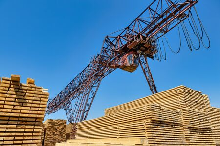 Industrial warehouse timber mill, finished products on a sawmill outdoors. Timber loading Gantry crane.