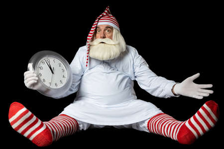 anta Claus in a nightgown and a nightcap sits on the floor and does not understand why he is late for Christmas. On a black background. Stok Fotoğraf