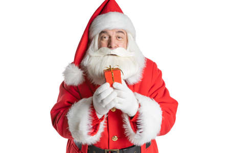 Portrait of an attractive and cheerful Santa Claus holding a holiday gift box in his hands. Isolated white background.