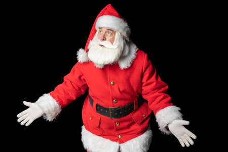 Old elderly man dressed as Santa Claus, clueless and confused, with open arms on a black background. Concept idea doubtful face.