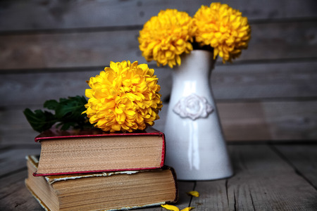 Flowers. Beautiful yellow chrysanthemum in a vintage vase. Cup of coffee. Bright Servais, cup and saucer .. Beautiful breakfast.Old books on a wooden background. photo