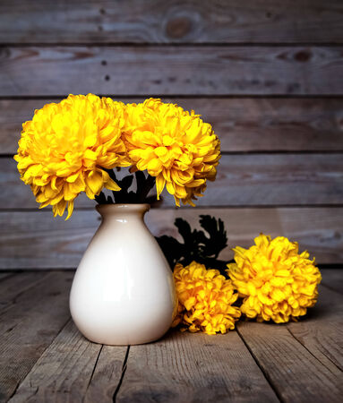 smells: Flowers. Beautiful yellow chrysanthemum in vintage pottery vase. Old wooden background