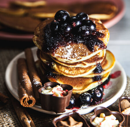 Picture of few pancakes with blackberries and sugar on wooden background photo