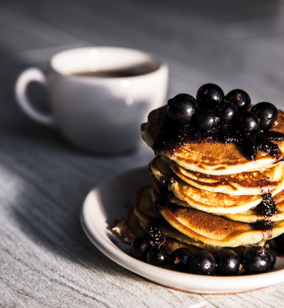 Pancakes with currant jam and a cup of tea photo