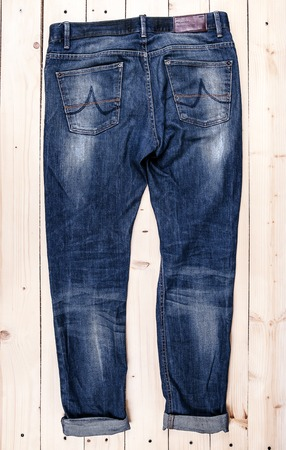 stride: Blue jeans trouser isolated on a wooden background