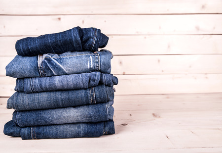 jeans pocket: fashionable clothes. pile of jeans on a wooden background