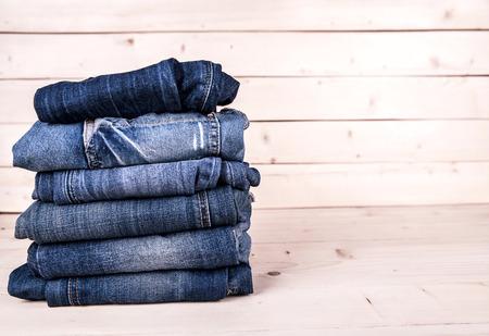 apilar: ropa de moda. pila de pantalones vaqueros en un fondo de madera
