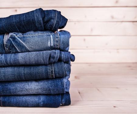 流行の服。木製の背景にジーンズの山