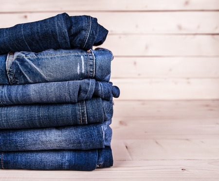 man in jeans: fashionable clothes. pile of jeans on a wooden background