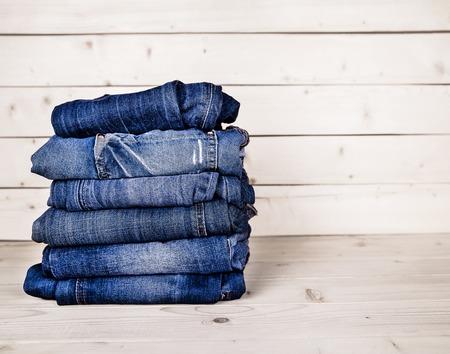 modieuze kleding. stapel jeans op een houten achtergrond Stockfoto