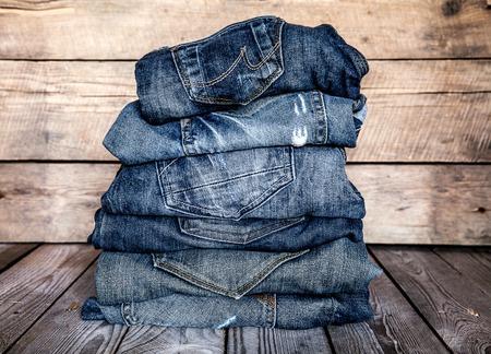 de vaqueros: ropa de moda. pila de pantalones vaqueros en un fondo de madera