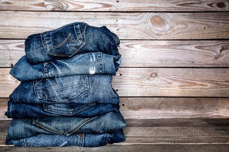 mezclilla: ropa de moda. pila de pantalones vaqueros en un fondo de madera