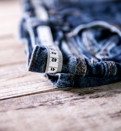 decreasing in size: jeans and centimeter on a wooden background. clothing Stock Photo