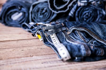 decreasing in size: jeans e centimetro su uno sfondo di legno. abbigliamento