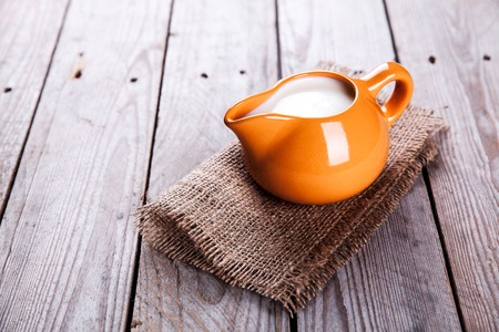 a jar stand: healthy drink. orange clay jug with milk in a rustic style on a wooden background