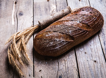 moody background: Rustic bread and wheat on an old vintage planked wood table. Dark moody background with free text space. Stock Photo