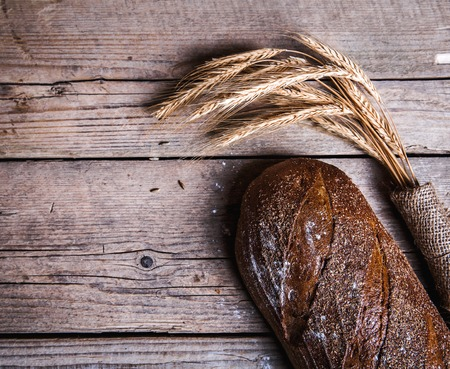 Rustiek brood en tarwe op een oude vintage planked houten tafel. Donkere moody achtergrond met vrije ruimte voor tekst.