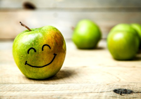fresh green apples in plate on wooden background. with a smile on apple Reklamní fotografie