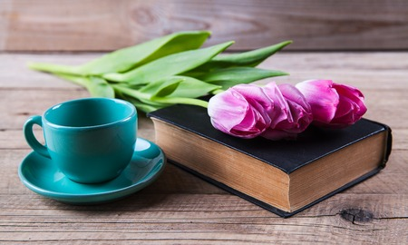 Kop van hete koffie op boek met bloemen op tafel Stockfoto