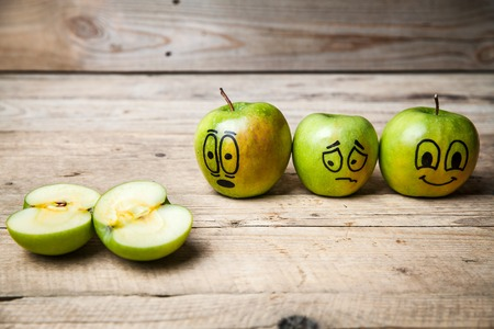painted face: Apples with painted face on wooden background