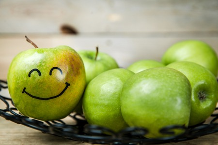 fresh green apples in plate on wooden background with a smile on apple