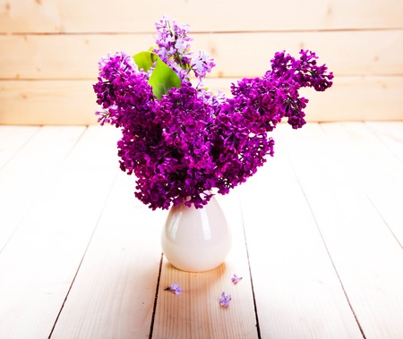 crowded space: Lilac Bouquet in ceramic jug against a white wooden wall. Stock Photo