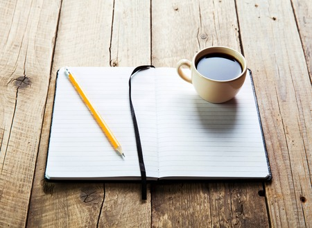 paper and pen: notebook pen and cup of coffee in wood table
