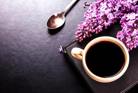 Zwarte koffie in een kopje, boek, een lepel en verse lila bloemen op zwarte achtergrond
