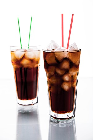 carbonation: two glasses of cola on white background.