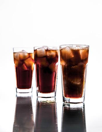 drie glazen en ijs op een witte achtergrond. frisdrank Stockfoto