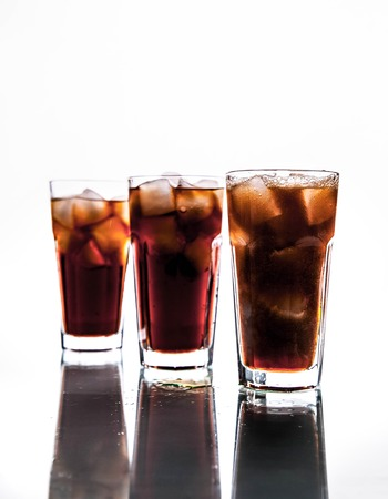three glasses and ice on a white background. soft drinks Stock Photo
