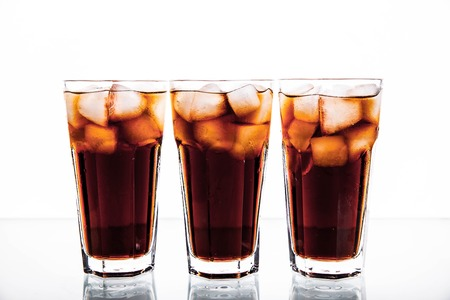 soft drinks: three glasses of cola and ice on a white background. soft drinks