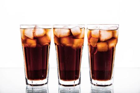 bebidas frias: tres vasos de refresco de cola y hielo sobre un fondo blanco. bebidas sin alcohol