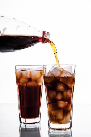 Cola is gieten in glas op witte achtergrond. frisdrank