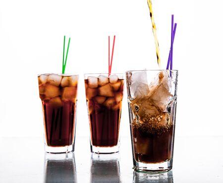 bebidas frias: tres vasos de refresco de cola con hielo y paja en un fondo blanco. bebidas sin alcohol