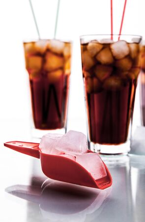 soft drinks: three glasses of cola with ice and straws on a white background. soft drinks Stock Photo