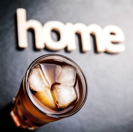 carbonation: cola with ice on a wooden background. Soft drinks symbol of home comfort