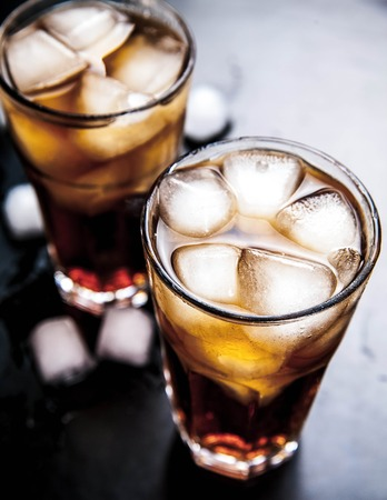 cola with ice on a wooden background. soft drinks Stock Photo