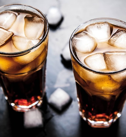 carbonation: cola with ice on a wooden background. soft drinks Stock Photo