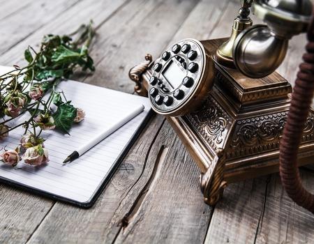 Oude vintage zwarte roterende telefoon en een boeket rozen op houten achtergrond Stockfoto