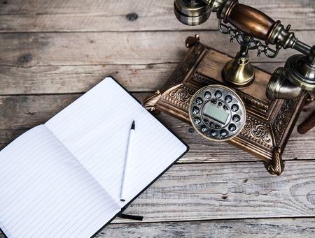 Vintage roterende telefoon en oude telefoon boek op tafel in de buurt van de muur