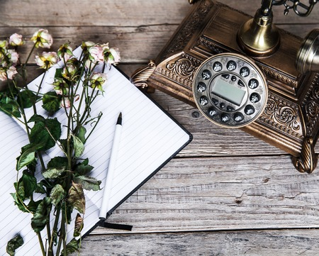 old furniture: Old vintage black rotary phone and a bouquet of roses on wooden background