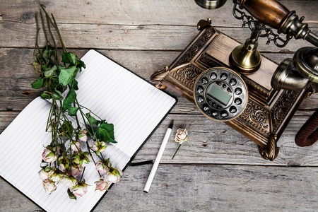 Old vintage black rotary phone and a bouquet of roses on wooden background