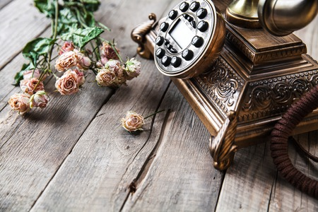 phone number: Old vintage black rotary phone and a bouquet of roses on wooden background