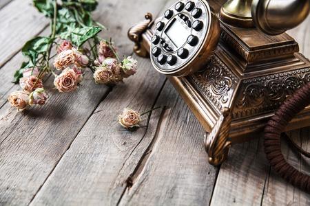 Oude uitstekende zwarte roterende telefoon en een boeket rozen op houten achtergrond